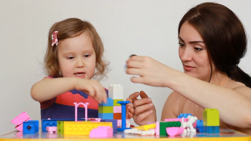 učitel : Mother and girl child busy building a constructor.