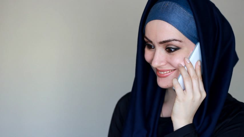 головной платок : Portrait of a beautiful Arab woman in a traditional headscarf hijab communicates on a mobile phone. A Muslim girl speaks on a white smartphone and smiles.