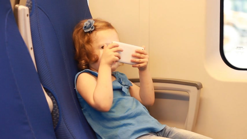 visto : Child girl entertaining with smartphone in train.