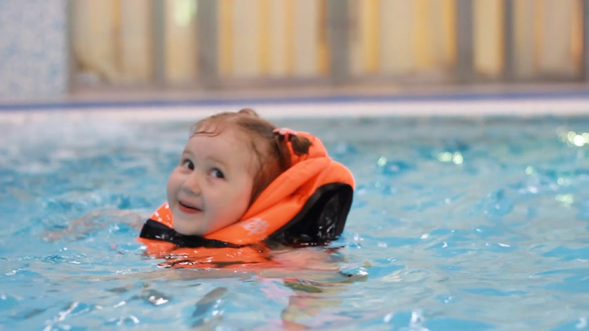 yelek : Child girl in the pool in a life jacket learns to swim. Swimming baby in the water