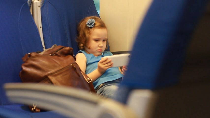ekspres : Girl child play with smartphone in train.