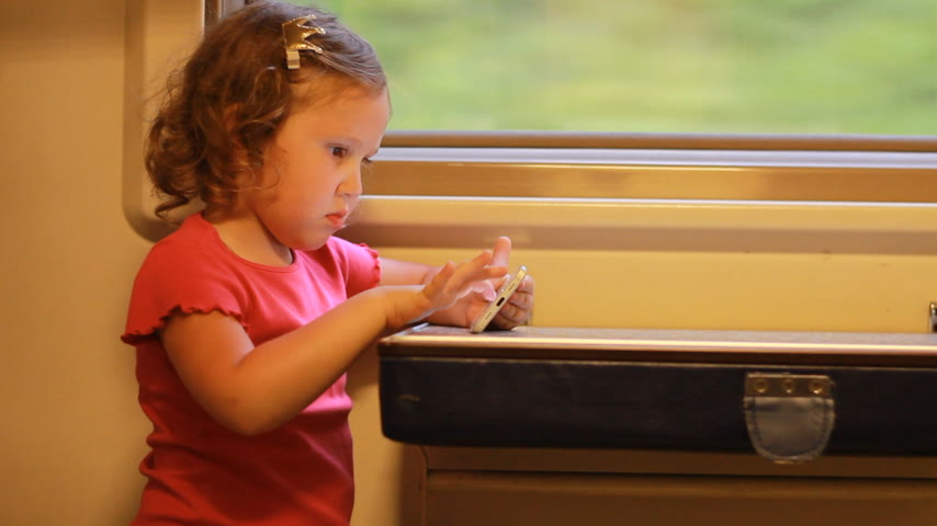 visto : Girl child play with smartphone in train. Baby playing game on the mobile phone in the road. Stock Footage