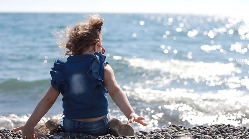 skákání : Child girl throws stones from the coast into the sea water.