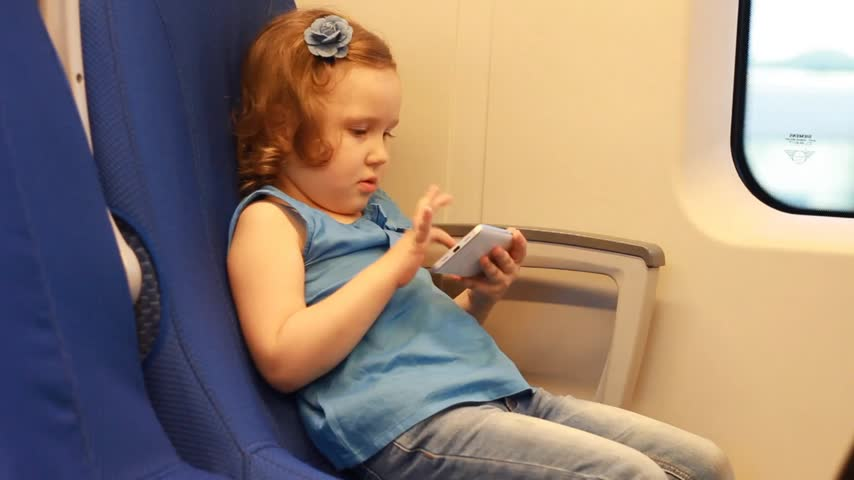 evez : Girl child play with smartphone in train.