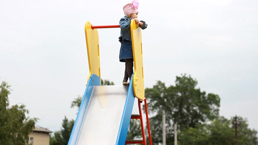 climbed : Child girl climbed high up. Baby play on the playground Stock Footage