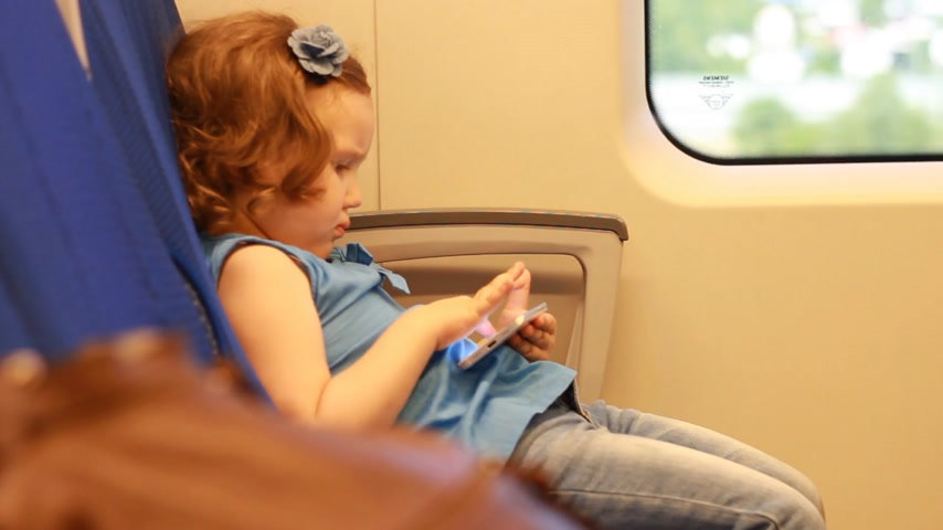 expressar : Girl child play with smartphone in train.