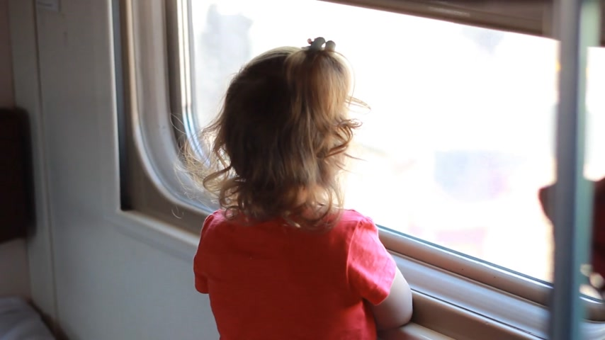 visto : Child girl is traveling by train. Baby travels by rail and and looks out the window. Stock Footage