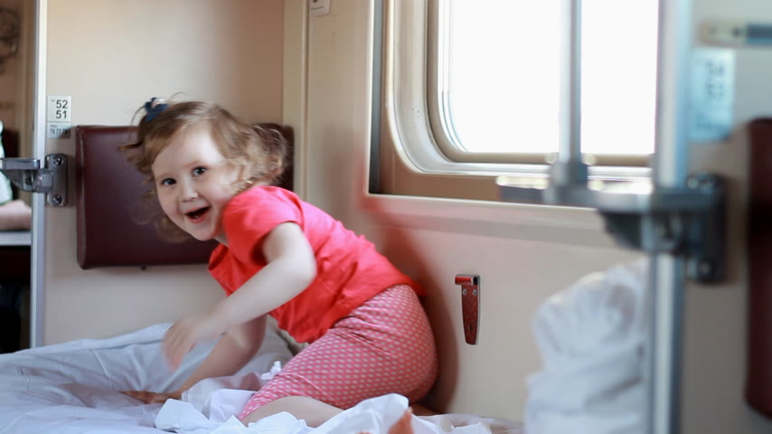 visto : Child girl is traveling by train. Baby travels by railway carriage and and getting ready to sleep