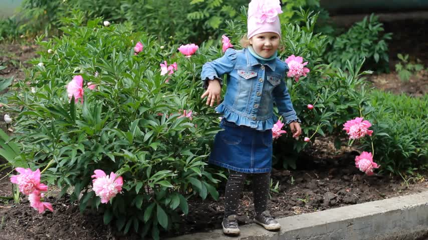 piwonie : Happy Child girl dances in the garden with peonies.