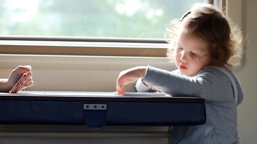 visto : Child girl play in the game with smartphone in train. Baby playing game on the mobile phone in the road. Stock Footage