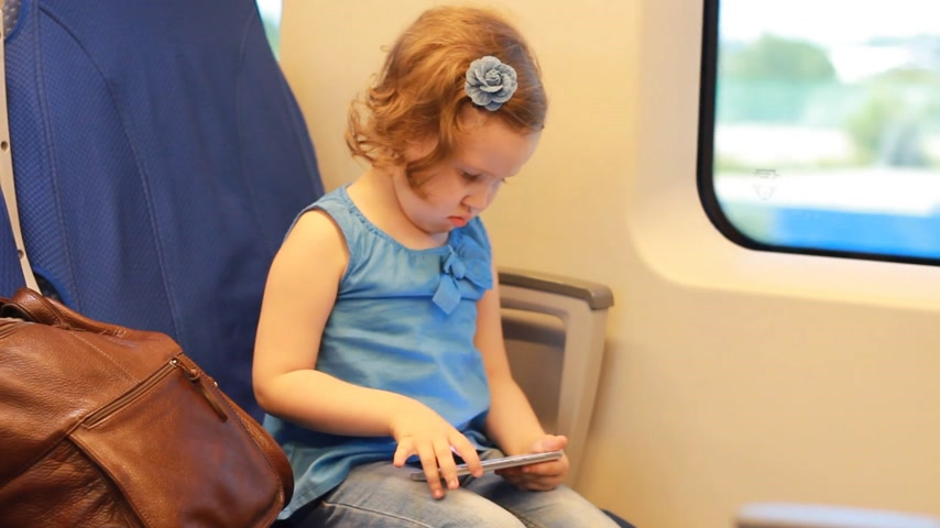 visto : Girl child play with smartphone in train.