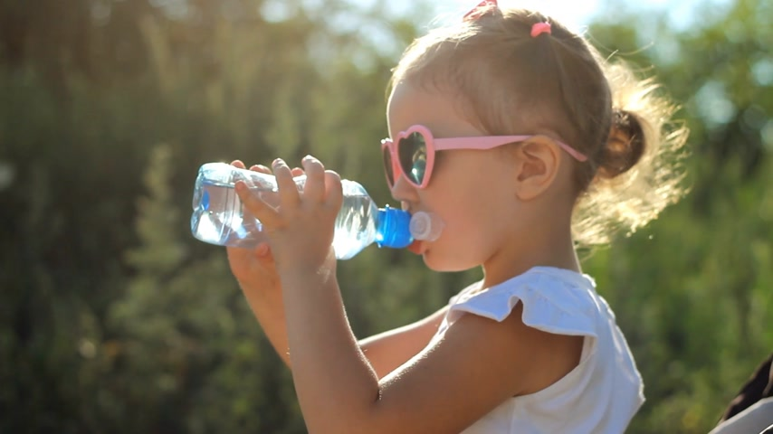 przedszkolak : Child girl in sunglasses drinks water from a bottle. Portrait child close-up on a sunny day.