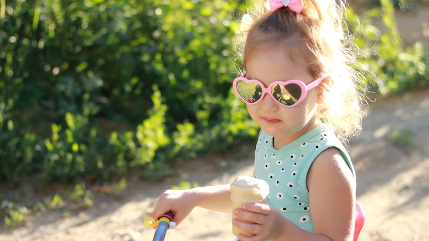 borrifar : Child girl eats ice cream in sunglasses on a sunny summer day.