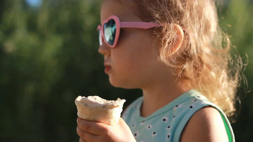 focus on foreground : Child girl eats ice cream in sunglasses on a sunny summer day.