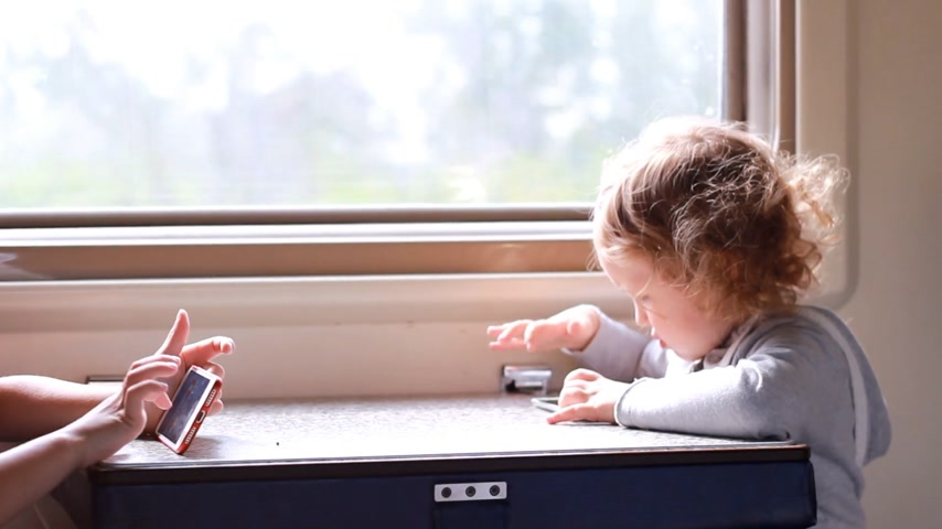 interest : Children girl and boy play in the game with smartphone in train.