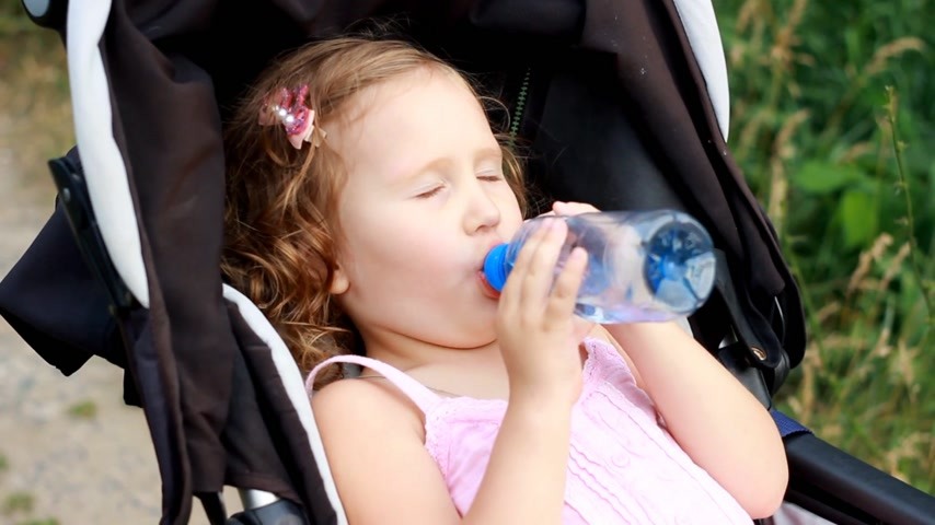 przedszkolak : Child girl lies in a baby carriage and drinks water from a bottle. Thirst in summer.