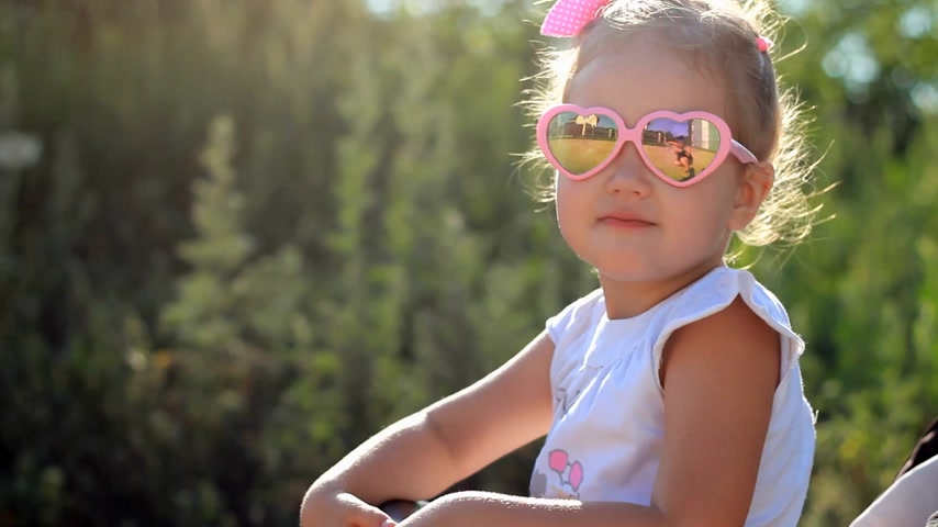 hátsó megvilágítású : Child in sunglasses is sitting in a stroller and sends air kisses at sunset. Stock mozgókép
