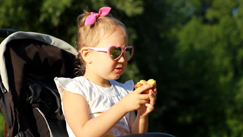 przedszkolak : Child in sunglasses is sitting in a stroller and eats an apple at sunset. Portrait baby girl close-up on a sunny day.