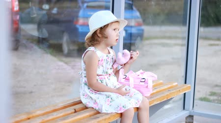 station de bus : Child girl tourist in a hat and with a backpack is sitting on a bench at a bus stop, waiting for transport for a further trip Vidéos Libres De Droits