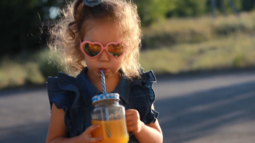 prevenzione : Child girl in sunglasses drinks smoothies in the rays of sunset on a summer day. Close up