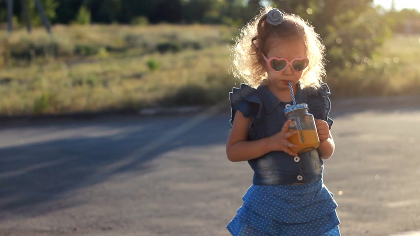 prevenzione : Child girl in sunglasses drinks smoothies in the rays of sunset on a summer day. Filmati Stock