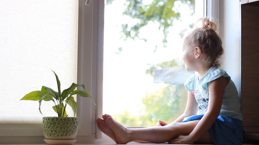 davanzale : A child sits on a window sill and looks out the window.