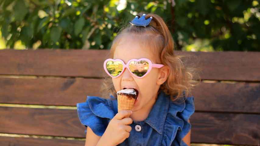 borrifar : Child girl eats ice cream in sunglasses on a sunny summer day. Portrait of a baby close-up