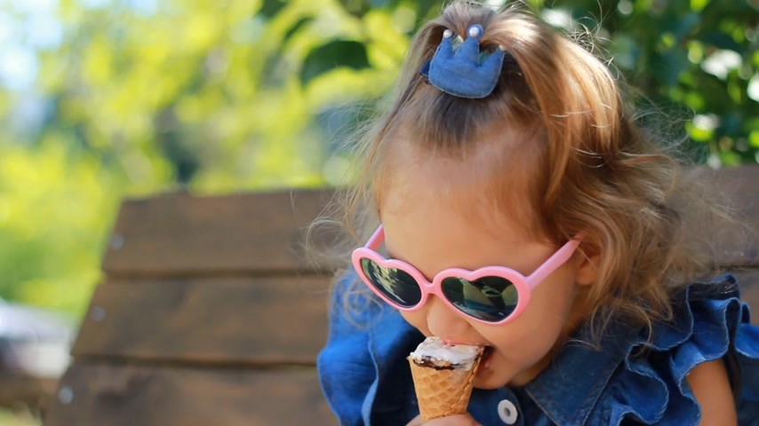 окропляет : Child girl eats ice cream in sunglasses on a sunny summer day. Portrait of a baby close-up