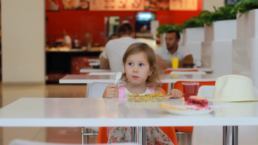 nibble : Fast food cafe. Child girl eats pilaf and drinks juice.