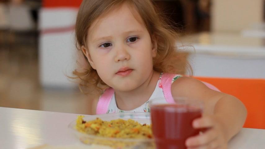 nibble : Child girl does not want to eat food in a fast food cafe or restaurant