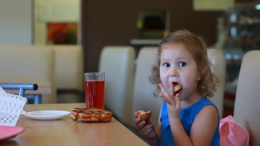 nibble : Child girl eats fast food and drinks juice in a cafe