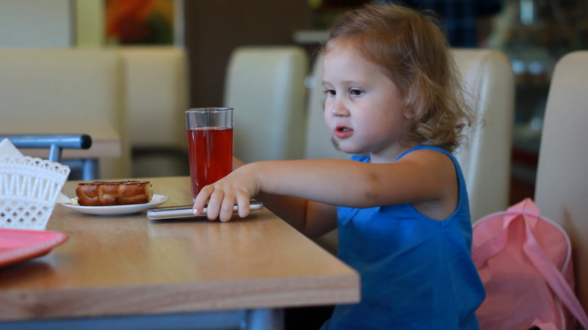 жевать : Child girl eats fast food and drinks juice in a cafe