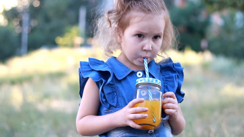 vejetaryenlik : Child drinks orange fresh in the summer. Portrait of a little girl who enjoys smoothies through a tube Stok Video
