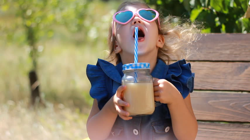 вегетарианство : Child girl in sunglasses drinks smoothies in the park on a sunny windy day