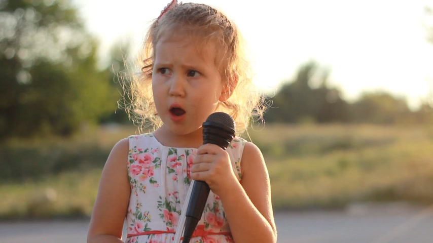 талант : Child girl sings into a microphone a song in the rays of a sunset in the summer.