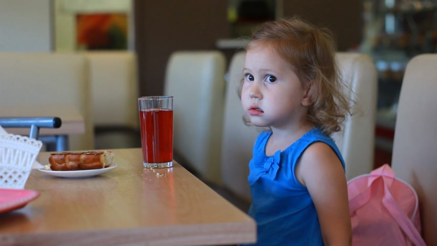 bun : Child girl eats fast food and drinks juice in a cafe