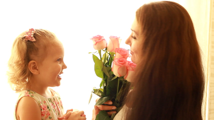 давать : Mom and daughter with a bouquet of flowers roses. The concept of a mothers day or birthday