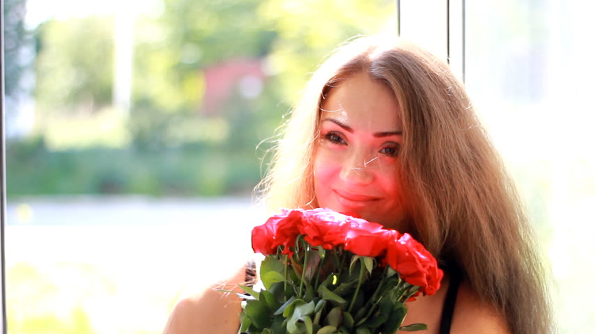 kacérkodás : Young woman is given a bouquet of red roses. Birthday. Celebration. Gift