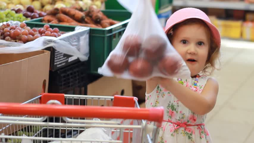 supermarket shelf : Child girl in the store chooses fruit. Grocery supermarket and shopping trolley Stock Footage