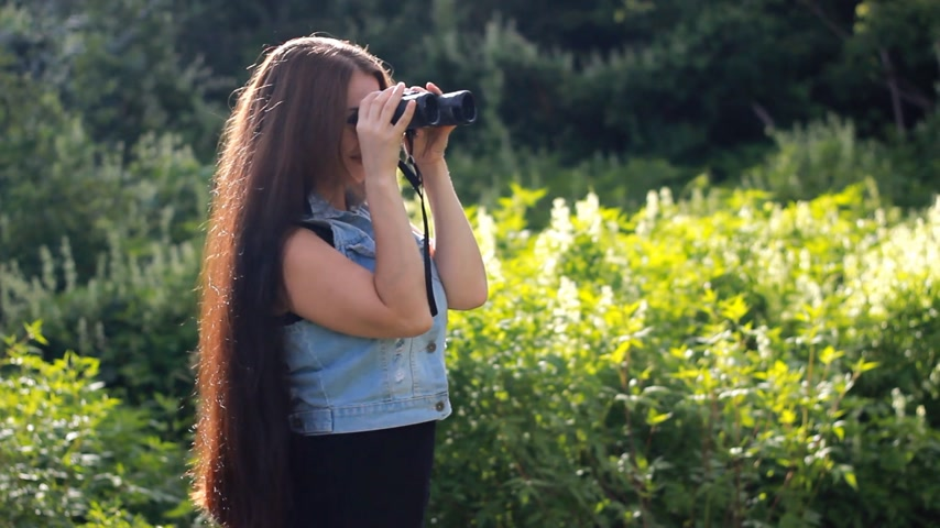 very : Young beautiful woman with very long hair looks through binoculars. Stock Footage