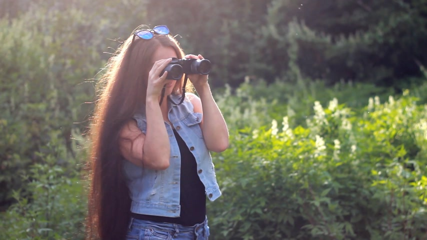 very : Beautiful girl with very long hair looks through binoculars. Stock Footage