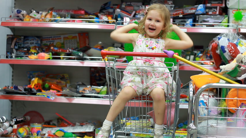 ulička : Childrens shop with toys. A child in a supermarket sits in the shopping cart