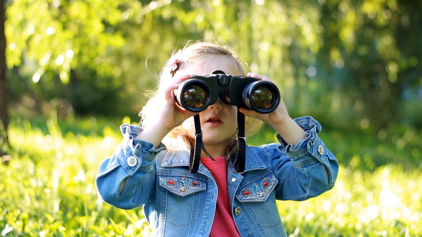 binocular : Child girl looking through binoculars and watching the nature