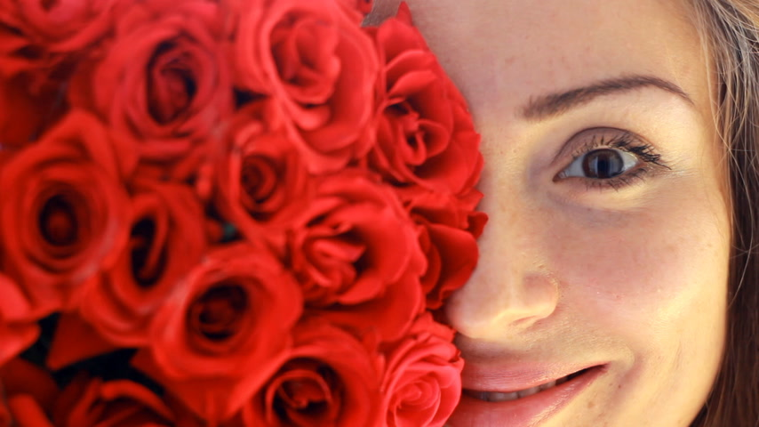 scented : Portrait of a young beautiful woman with a bouquet of flowers of red roses.