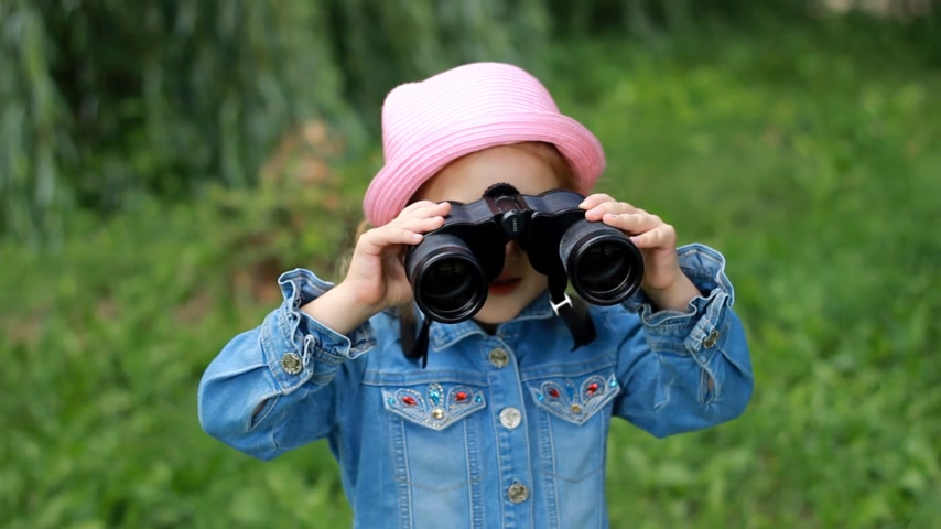boulders : Child girl looking through binoculars and watching the nature