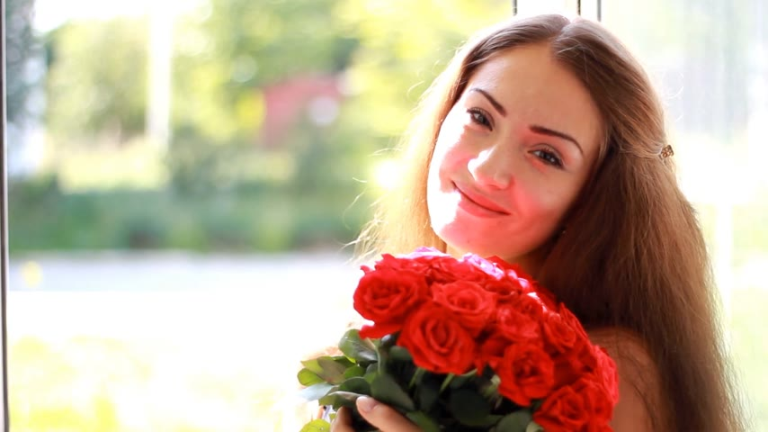 kacérkodás : Young woman with a bouquet of red roses near an open window. A beautiful girl enjoys the aroma of flowers Stock mozgókép