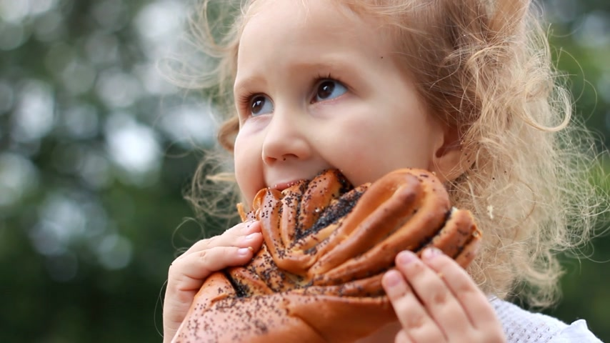 bagietka : Child girl eating loaf with poppy seeds outdoor.