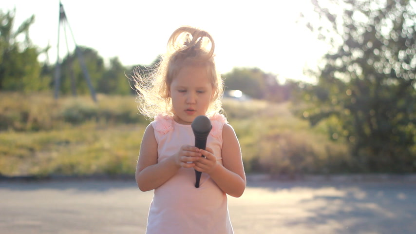 chmiel : Child girl sings into a microphone a song in the rays of a sunset in the summer. Talented child is a musical voice.