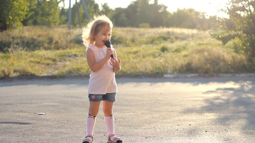 рэп : Child girl sings into a microphone a song in the rays of a sunset in the summer. Talented child is a musical voice.
