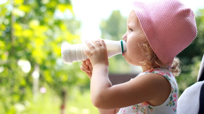 nyel : Child girl drinks a milk drink from a bottle or kefir, smiles and shows a white mustache from yogurt.